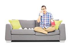 Trauriger Kerl, der auf einer Couch sitzt und seine Augen vom Schreien abwischt Stockbild