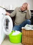 Trauriger Kerl, der Waschmaschine verwendet Stockfotografie
