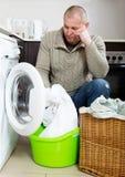 Trauriger Kerl, der Waschmaschine verwendet Stockbilder