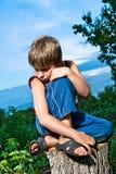 Trauriger kleiner Junge, der auf einem Stumpf sitzt Stockfotos