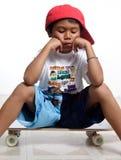 Trauriger kleiner Junge, der auf seinem Skateboard sitzt Stockfoto