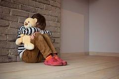 Trauriger kleiner Junge, der gegen die Wand in der Verzweiflung sitzt Lizenzfreies Stockbild
