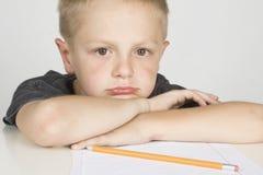 Trauriger kleiner Junge, der seine Heimarbeit tut Stockfotografie