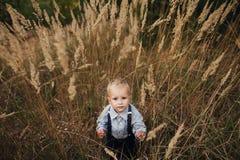 Trauriger kleiner Junge im hohen Gras Lizenzfreie Stockbilder