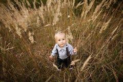 Trauriger kleiner Junge im hohen Gras Stockfotos
