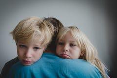 Trauriger kleiner Junge und Mädchen, die Vater, Familie in der Sorge umarmt stockbilder