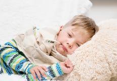 Trauriger kranker Junge mit dem Thermometer, der in Bett legt Stockbilder