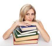 Trauriger Kursteilnehmer auf einem Stapel der Bücher. Stockfotos