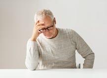 Trauriger älterer Mann, der bei Tisch sitzt Stockfotos