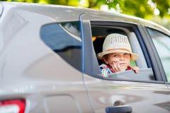 Trauriger müder Kinderjunge, der im Auto während des Staus sitzt Lizenzfreie Stockbilder