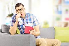 Trauriger Mann auf einem Sofa, das seine Augen von zu Hause schreien abwischt Stockfotos