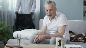 Trauriger Mann, der auf Couch sitzt und Kamera, männliche Krankenschwester holt Rollstuhl untersucht Lizenzfreie Stockfotos
