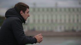 Trauriger Mann, der auf der Brücke in der Mitte von St Petersburg steht stock footage