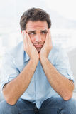 Trauriger Mann, der auf der Couch weg schaut sitzt Lizenzfreie Stockfotografie