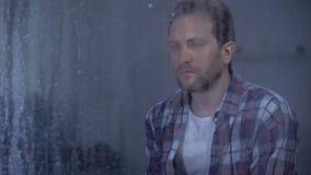 Trauriger Mann, der durch Fenster bei dem regnerischen Wetter, denkend an Lebenproblem schaut stock footage