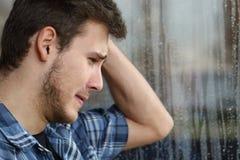 Trauriger Mann, der durch Fenster ein regnerischen Tag schaut Stockfotografie