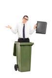 Trauriger Mann, der in einem Abfalleimer steht Stockbild