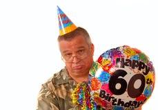 Trauriger Mann, der einen Ballon für ein 60. Geburtstagteil anhält Stockbild