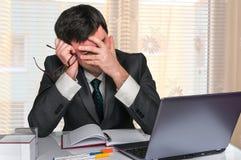 Trauriger Mann, der an Laptop im Büro arbeitet lizenzfreies stockfoto