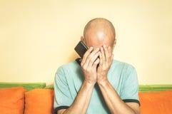 Trauriger Mann, der seinen Handy in seinen Händen halten und Schrei, weil seine Freundin oben mit ihm über der Textnachricht brec lizenzfreies stockbild