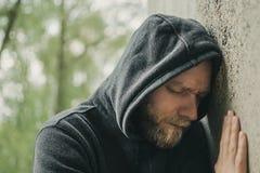 Trauriger Mann, der seinen Kopf an einer Wand lehnt stockfotografie
