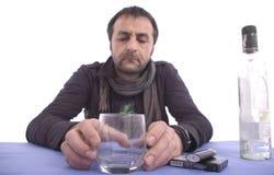 Trauriger Mann, der am Tisch sitzt Lizenzfreies Stockfoto