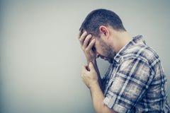 Trauriger Mann des Porträts eins, der nahe einer Wand und Abdeckungen sein Gesicht steht lizenzfreie stockfotografie