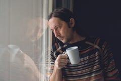 Trauriger Mann am Fenster, der Kaffee trinkt Stockbild