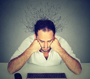 Trauriger Mann mit dem Gehirn, das in die Linien betrachten Computertastatur schmilzt Stockfotografie