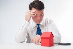 Trauriger Mann mit einem Lupen- und Papierhaus Lizenzfreies Stockbild