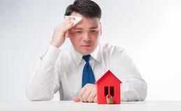 Trauriger Mann mit einem roten Papierhaus Stockfotos