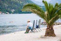 Trauriger Mann sitzt auf dem Strand am Sturmtag Kotor Schacht, Montenegro Stockfotos