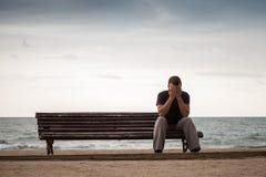 Trauriger Mann sitzt auf einer alten Holzbank auf der Seeküste Stockbilder