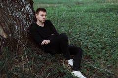 Trauriger Mann sitzt unter einem Baum und raucht Stockfotos