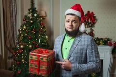 Trauriger Mann stellt auf dem Kasten mit einem Geschenk dar Stockbild