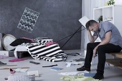 Trauriger Mann umgeben durch Verwirrung stockfoto