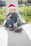 Trauriger Mischrasse-Junge mit Santa Hat und Zuckerstange Stockfotos