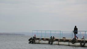 Trauriger nachdenklicher Mann geht auf den Pier und geht zum Rand stock video footage