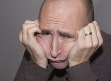 Trauriger oder frustrierter Mann, der seinen Kopf in seinen Händen stillsteht Stockfotos