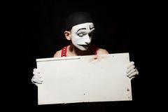 Trauriger Pantomime, der schmutziges Blatt des Weißbuches in den Händen hält Stockbild