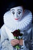 Trauriger Pantomime Pierrot mit einer roten Rose Lizenzfreie Stockfotografie