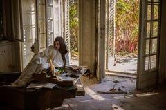 Trauriger Pianist, der gebrochenes Klavier an verlassenem Haus spielt Stockfotografie