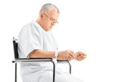 Trauriger reifer Mann, der in einem Rollstuhl sitzt Lizenzfreies Stockbild