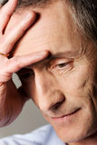 Trauriger reifer Mann, der seinen Kopf berührt Lizenzfreies Stockfoto