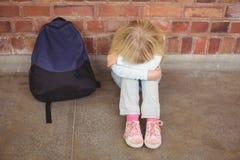 Trauriger Schüler, der allein auf dem Boden sitzt stockfoto