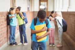 Trauriger Schüler, der von den Mitschülern am Korridor eingeschüchtert wird Lizenzfreies Stockfoto