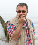 Trauriger schauender älterer Mann auf dem Strand Stockfoto