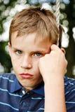 Trauriger schauender Junge, der auf einem Schwingen sitzt Stockbilder
