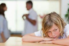 Trauriger schauender Junge mit dem Kämpfen parents hinter ihm Lizenzfreies Stockfoto