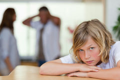 Trauriger schauender Junge mit der Argumentierung parents hinter ihm Stockfotografie